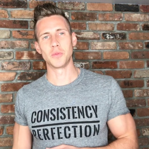 """Mike Vacanti wearing a grey shirt which reads, """"Consistency Over Perfection"""""""